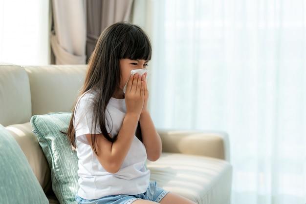 Aziatisch meisje ziek en verdrietig met niezen op neus