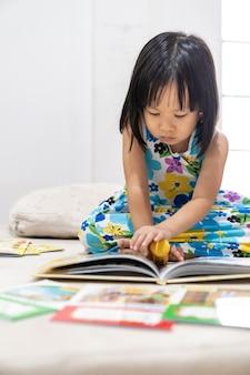Aziatisch meisjeskind dat interactief boek in de woonkamer thuis leest als thuisonderwijs
