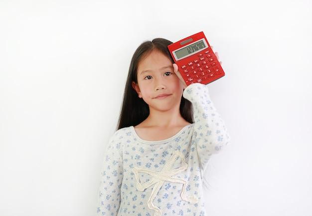 Aziatisch meisjeskind die rekenmachine op witte achtergrond tonen. kind met een rode rekenmachine