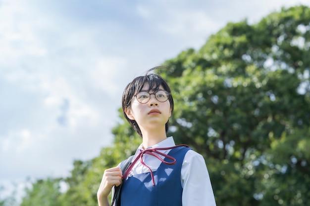 Aziatisch middelbare schoolmeisje dat met glazen de hemel bekijkt