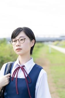 Aziatisch middelbare schoolmeisje met kort zwart haar dat een bril draagt