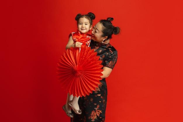 Aziatisch moeder en dochterportret dat op rode muur in traditionele kleding wordt geïsoleerd
