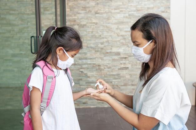 Aziatisch moeder en kindmeisje die beschermingsmasker dragen die desinfecterende gelwashand gebruiken om besmetting door virus en bacteriën te voorkomen voor en na gaan naar buiten voor het stoppen van coronavirus covid19-uitbraak.