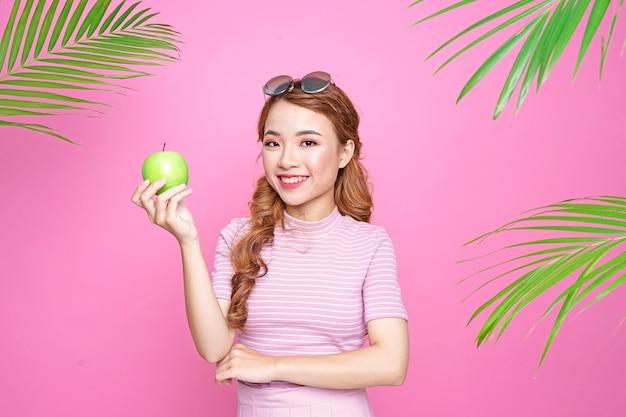 Aziatisch mooi aantrekkelijk vrij jong meisje in de zomerconcept met jus d'orange en palmbladen