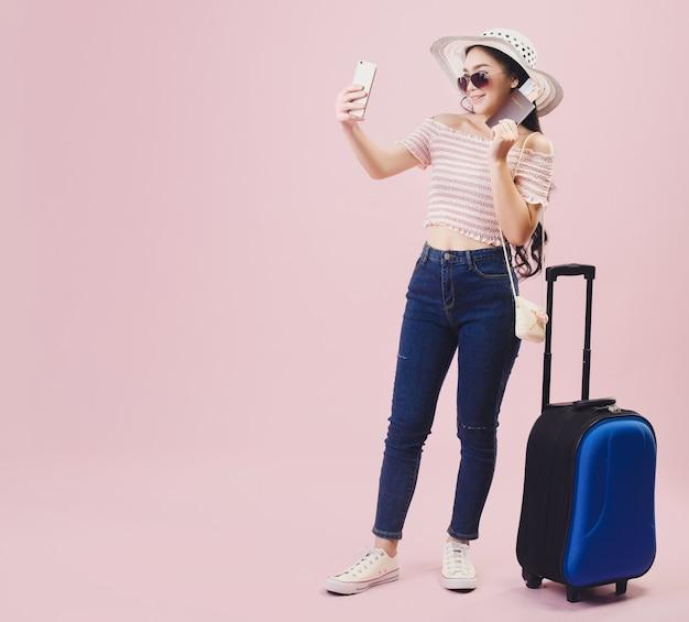 Aziatisch mooi jong meisje dat lacht, draagt een zonnebril en neemt een selfie met een smartphone, jonge vrouwen backpacker nemen een selfie en houden een paspoort vast op een roze studioachtergrond. pastelroze toonfilters.