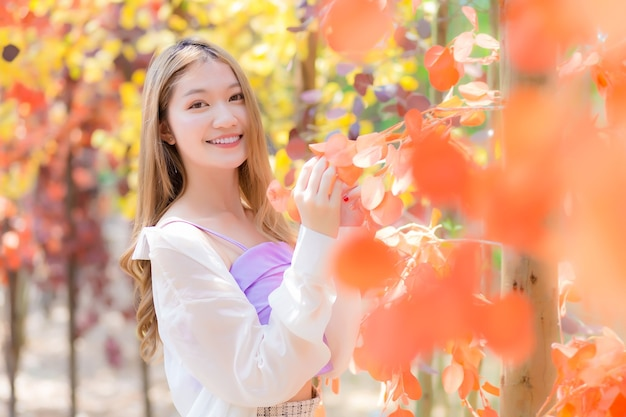 Aziatisch mooi meisje met bronzen haar staat tussen oranje bos in levendig en geluksthema.