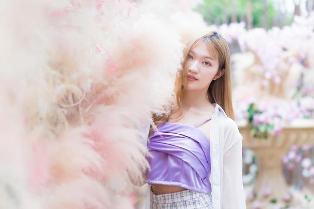 Aziatisch mooi meisje met lang bronshaar dat een korte rok en witte stands met lange mouwen draagt