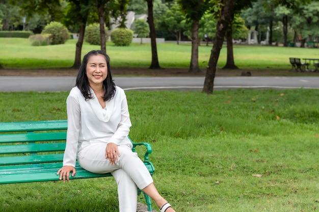 Aziatisch mooi portret van hogere vrouw die en bij het park denkt ontspant.