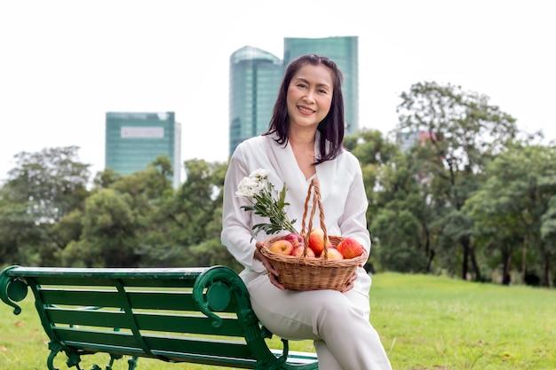 Aziatisch mooi portret van hogere vrouw met fruitmand en bloem in het park.