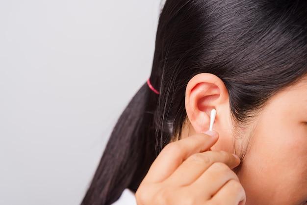 Aziatisch mooi vrouwen schoonmakend oor en het gebruiken van katoenen zwabber