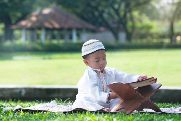Aziatisch moslimjongetje leest de koran in het park, islamconcept,
