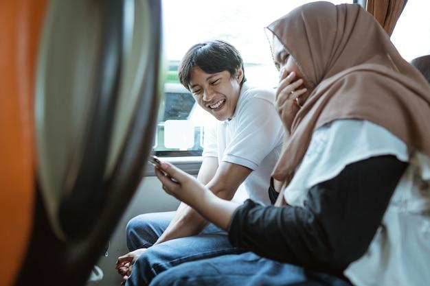 Aziatisch moslimkoppel lacht wanneer ze de video op hun mobiele telefoons zien terwijl ze in de bus zitten