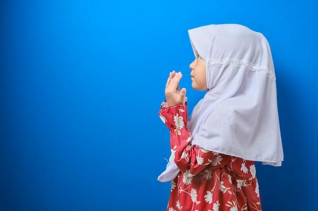 Aziatisch moslimmeisje dat hijab draagt en bidt met een lege ruimte naast haar