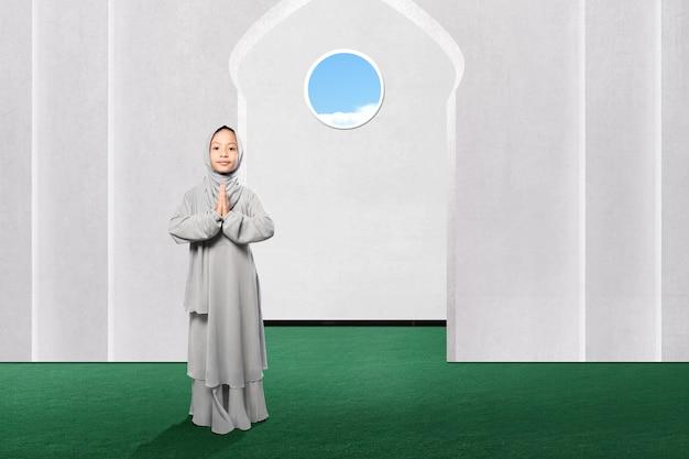 Aziatisch moslimmeisje in sluier met groetgebaar op de moskee