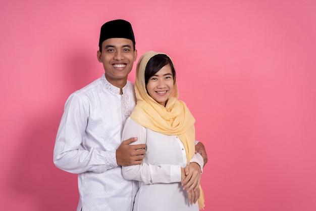 Aziatisch moslimpaar dat aan camera glimlacht