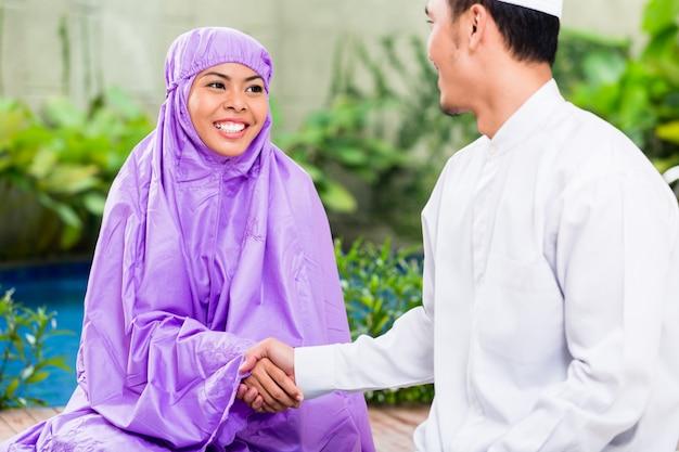 Aziatisch moslimpaar, man en vrouw, die thuis bidden