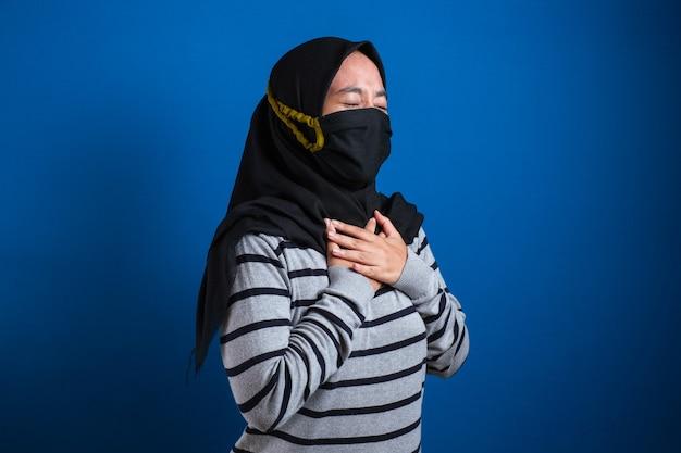 Aziatisch moslimstudentmeisje dat masker draagt dat pijn in haar borst voelt, gebaar dat linkerborst houdt. blauwe achtergrond