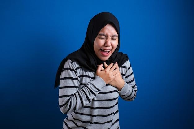 Aziatisch moslimstudentmeisje dat pijn in haar borst voelt, gebaar met linkerborst. blauwe achtergrond