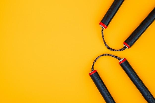 Aziatisch nunchaku-wapen op een oranje oppervlakte