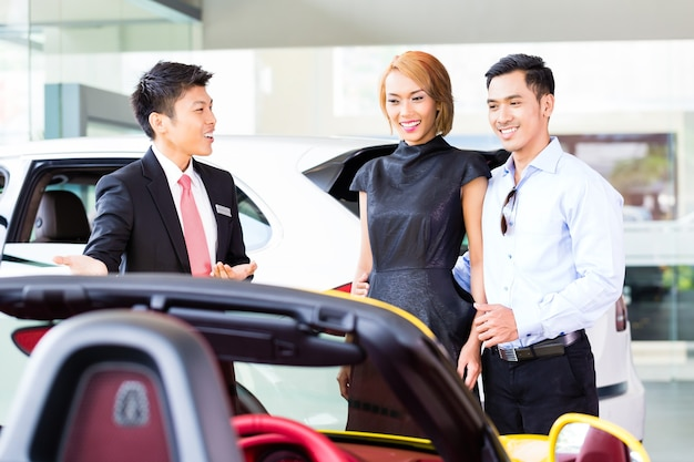 Aziatisch paar dat auto in autodealer koopt die de verkoper raadpleegt