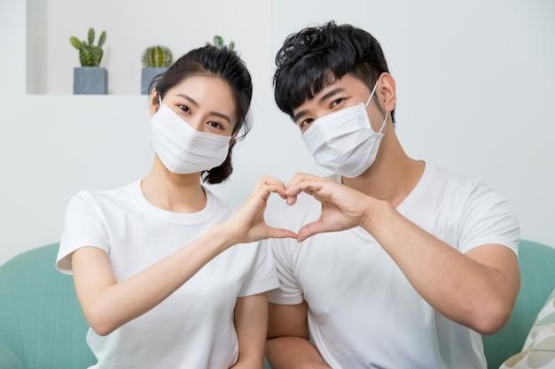Aziatisch paar dat beschermend gezichtsmasker draagt en thuis vorm van hart maakt door hun handen.