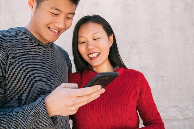 Aziatisch paar dat de mobiele telefoon bekijkt.