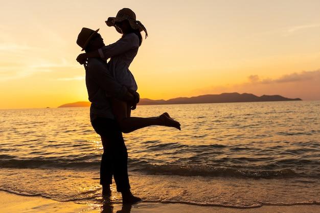 Aziatisch paar dat hun gevoel uitdrukt terwijl status bij strand, jonge parenomhelzing bij het overzees bij zonsondergang
