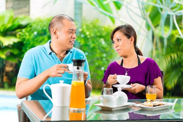 Aziatisch paar dat koffie op huisportiek heeft