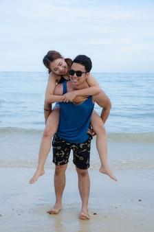 Aziatisch paar dat op strand, met meisjesrit loopt op zijn rug