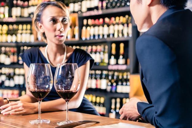 Aziatisch paar dat rode wijn drinkt