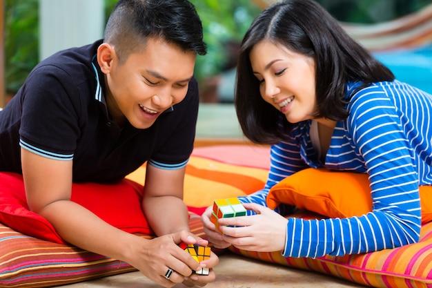 Aziatisch paar dat thuis met magische kubus speelt