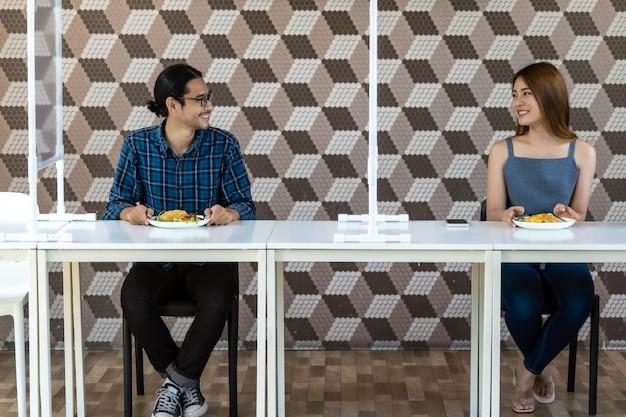 Aziatisch paar dat uit bij nieuw normaal restaurant eet