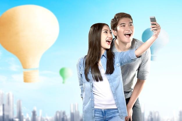 Aziatisch paar die een selfie met kleurrijke luchtballon nemen die met stadsachtergrond vliegen
