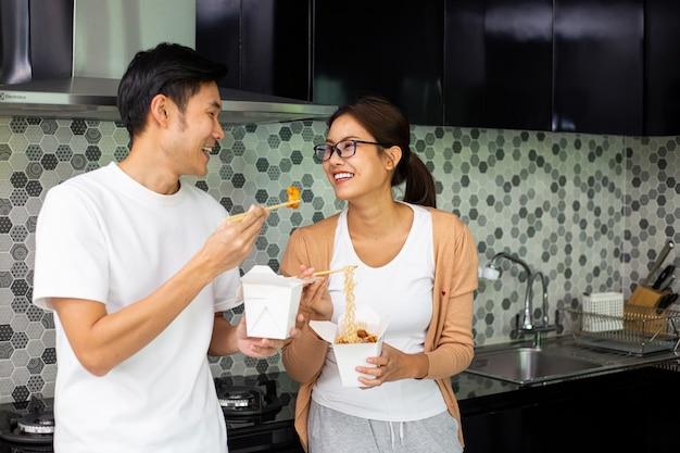Aziatisch paar die instantnoedels samen eten in de keuken. geniet van een gezonde maaltijd. levensstijl voor het avondeten en blijf thuis. vrouw die instant noedels eet.