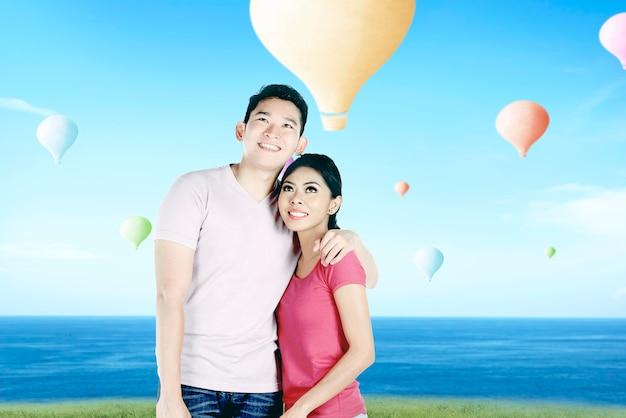 Aziatisch paar die kleurrijke luchtballon bekijken die met blauwe hemelachtergrond vliegen