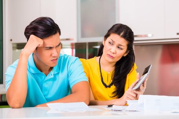 Aziatisch paar die onbetaalde rekeningen vechten