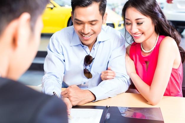 Aziatisch paar die verkoopcontract voor auto ondertekenen bij het handel drijven