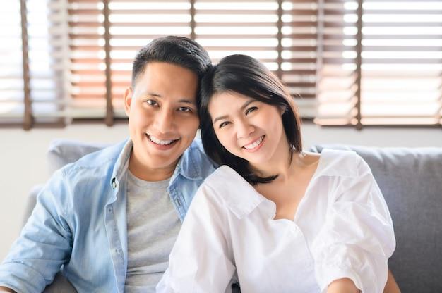 Aziatisch paar in liefde het glimlachen thuis ontspannend op bank