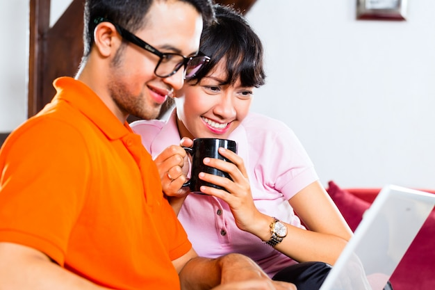 Aziatisch paar op de bank met laptop