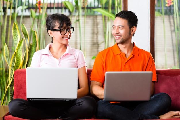 Aziatisch paar op de laag met laptop