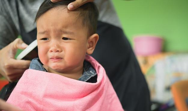 Aziatisch peuterkind dat zijn eerste kapsel krijgt.
