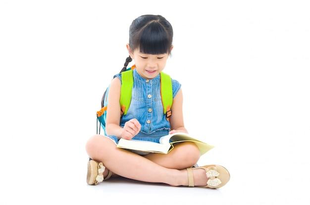 Aziatisch peutermeisje met schooltas en boeken die op de vloer zitten