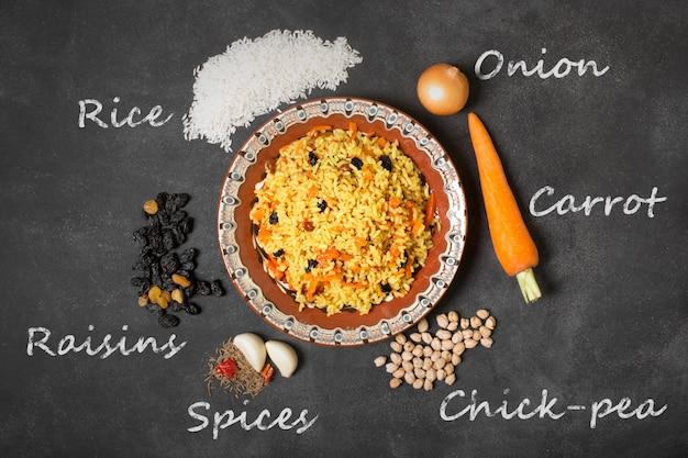 Aziatisch pilau op de zwarte tafel. inscriptie van rauwe ingrediënten