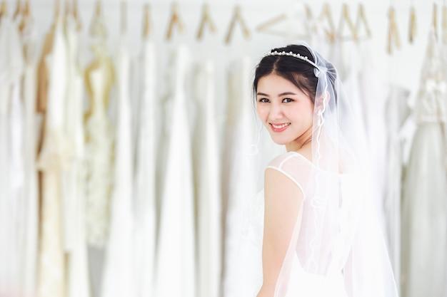 Aziatisch portret van leuke dame die gelukkige dragende huwelijkskleding glimlacht