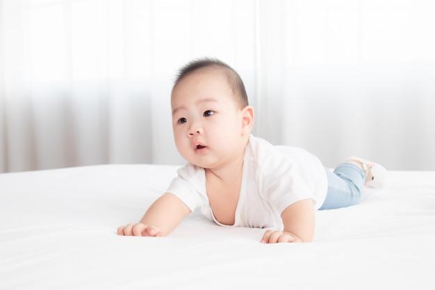 Aziatisch schattig aanbiddelijk baby gezond jongen goed humeur glimlachen lachend liggen op de slaapkamer opleving spelen met camera of moeder, baby peuter, zachte huid gelukkig gezicht uitdrukking op zoek moeder