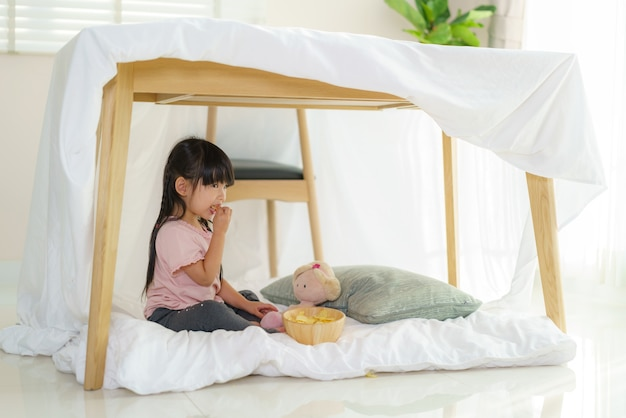 Aziatisch schattig klein meisje eten snack zittend in een deken fort in de huiskamer