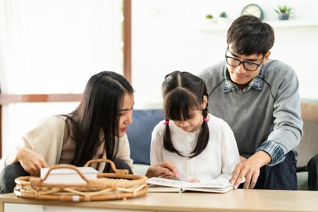 Aziatisch schattig meisje het lezen van verhalenboek met haar pappa en mamma in de woonkamer.