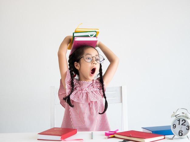 Aziatisch schattig meisje met boek op het bureau