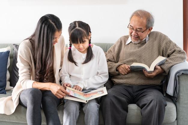 Aziatisch schattig meisje verhaal cartoon boek lezen met haar moeder en grootvader