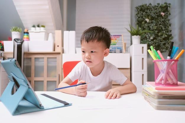 Aziatisch schooljongenjong geitje die de computer die van tabletpc thuiswerk thuis bestuderen gebruiken tijdens zijn online les, afstandsonderwijs, homeschooling concept
